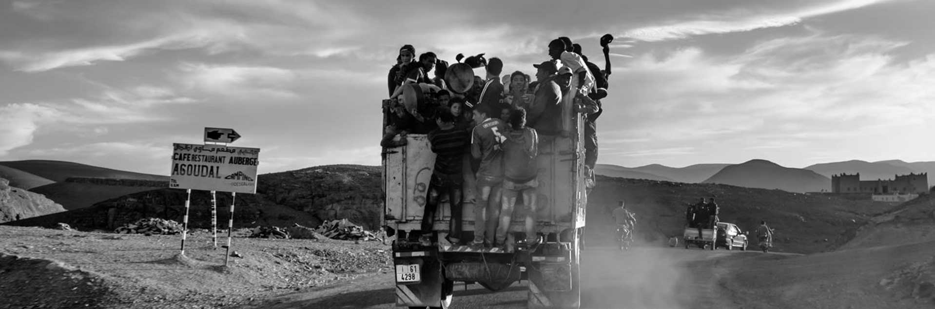 Header photo of a Truck full of People Driving Through Morocco
